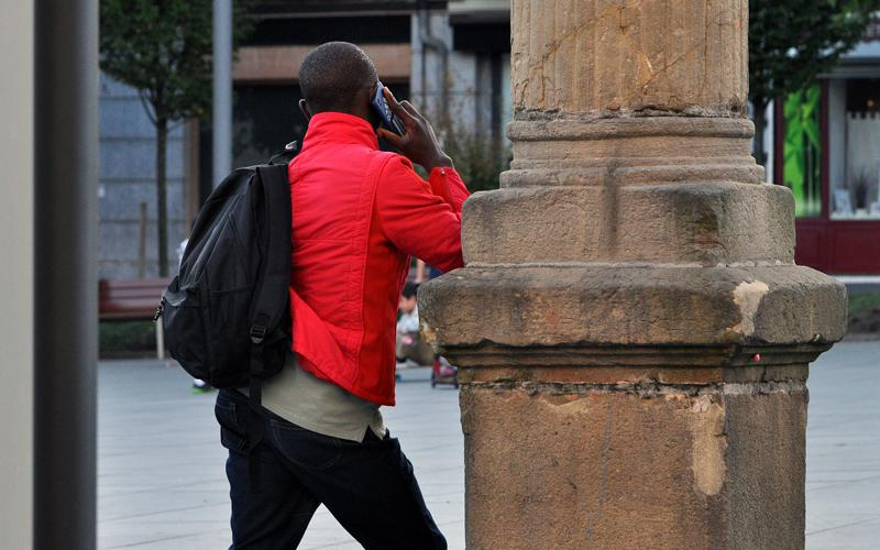 Un migrante habla el miércoles por la tarde en la plaza de San Juan de Irun por teléfono, esperando el momento de ir por la noche al otro lado del Bidasoa. Argazkia: bisadoa.hitza.eus